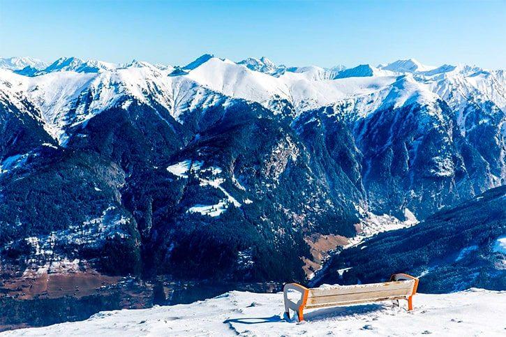 Скамейка в горнолыжный курорт Бад Гаштайн в заснеженных зимних горах, Австрия, Зальцбург