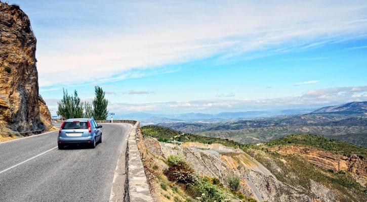 Вождение автомобиля по асфальтированной дороге вдоль горного склона в испанской Сьерра-Невада